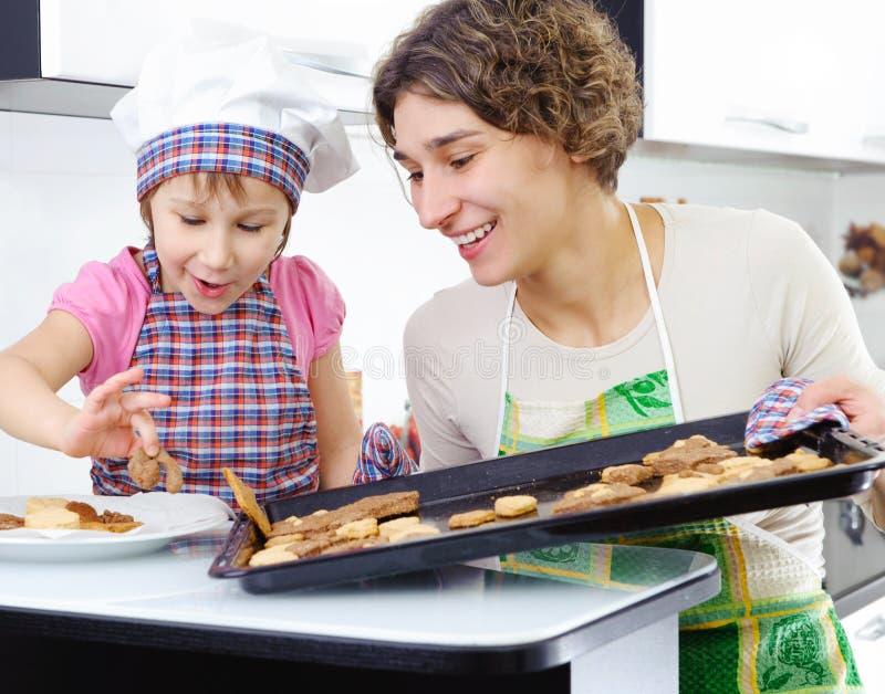 Petite fille et mère avec les biscuits cuits au four images stock