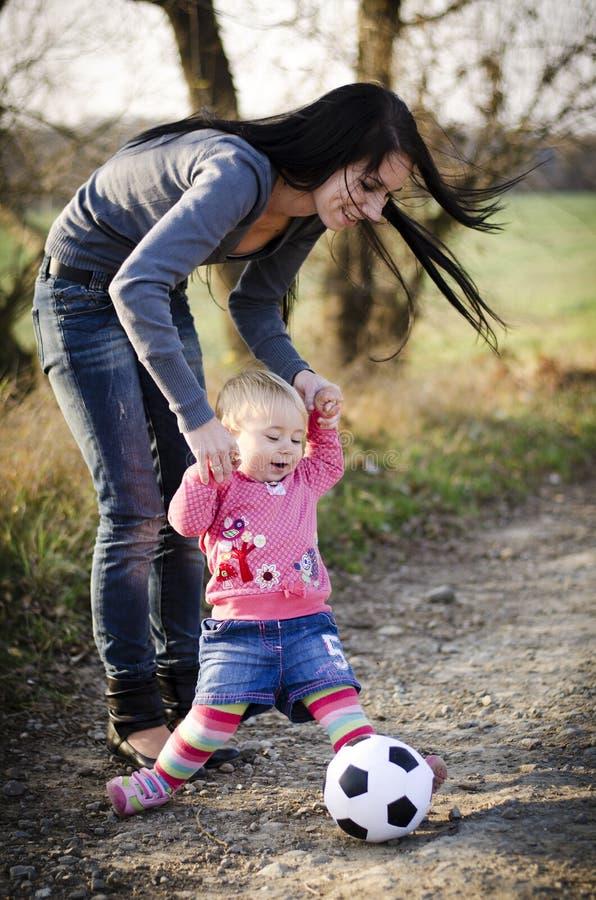 petite fille et mère avec une boule images stock