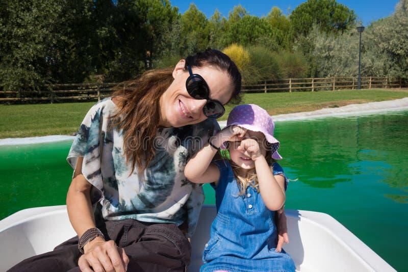 Petite fille et mère posant dans un bateau photo stock
