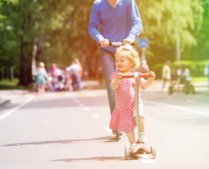 Petite fille et père heureux sur des scooters dans photo libre de droits