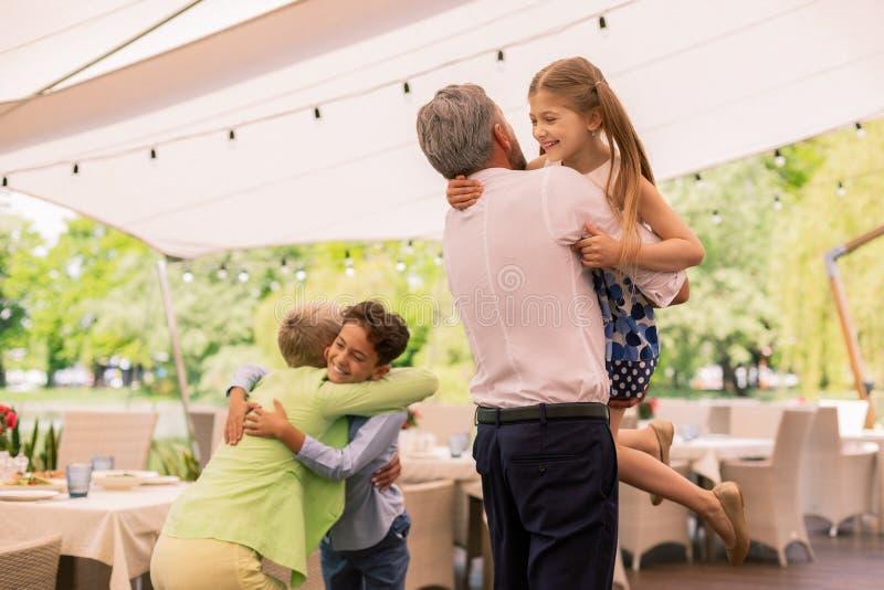 Petite-fille et petit-fils aimants étreignant des grands-parents images libres de droits