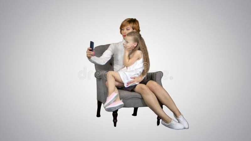 Petite fille et sa mère prenant le selfie sur le fond blanc photos stock