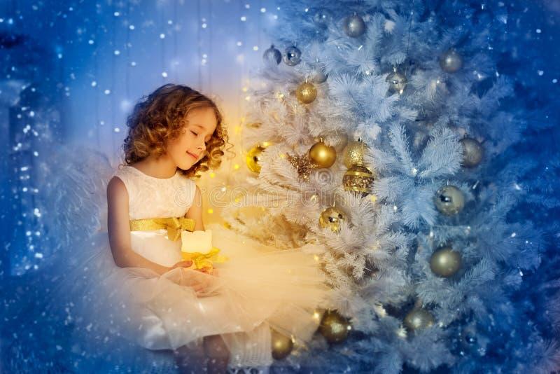 Petite fille et sapin de Noël, heureux, enfant aux chandelles Envie d'un cadeau de Noël image stock