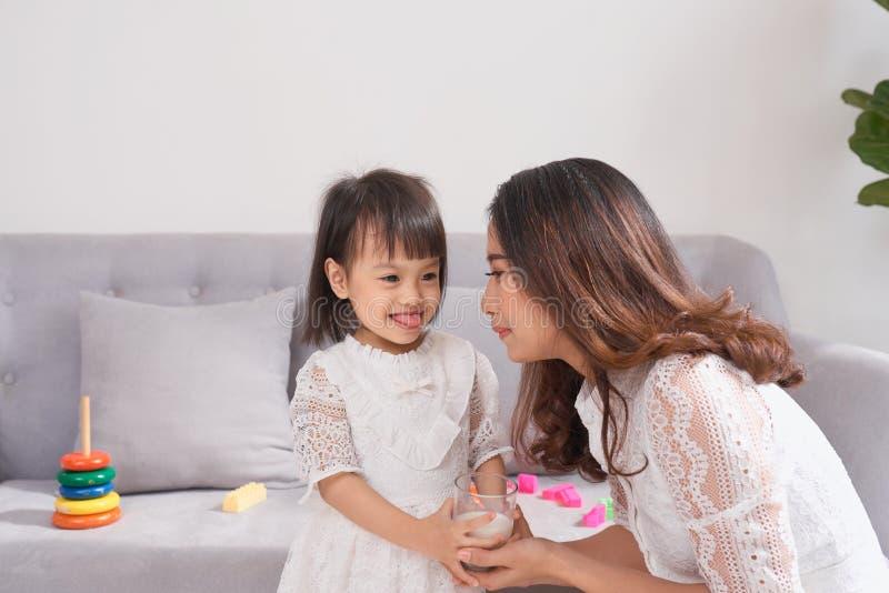 Petite fille et son lait boisson de maman se reposant sur le sofa à la maison M photographie stock