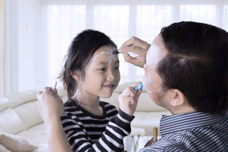 Petite fille et son père faisant la peinture de visage image libre de droits