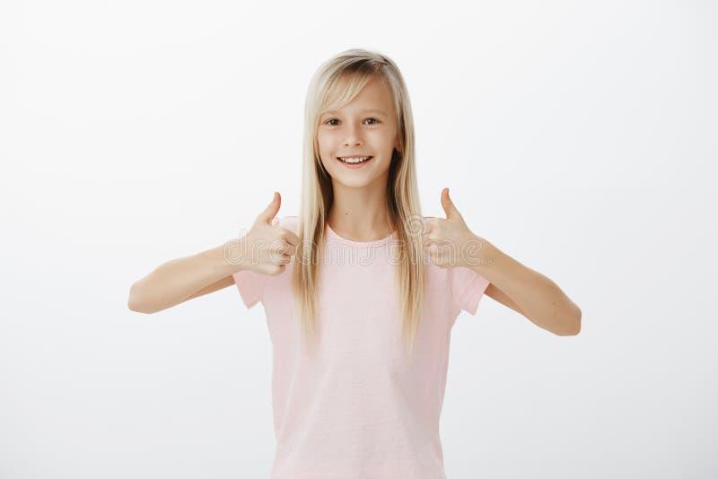 Petite fille européenne positive belle avec les cheveux justes naturels, montrant des pouces et souriant largement, idée avec app photo libre de droits