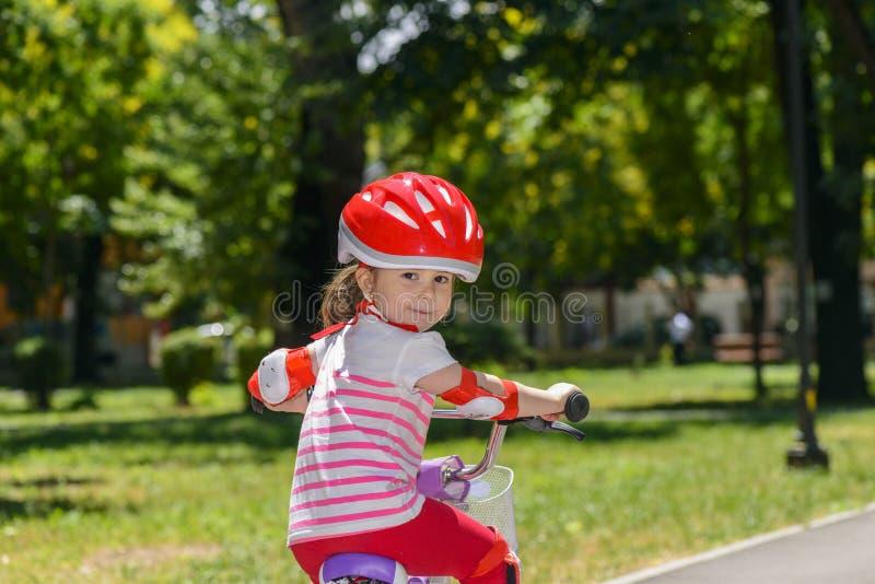 Petite fille expressive avec le casque de sécurité rouge coloré montant une bicyclette images libres de droits