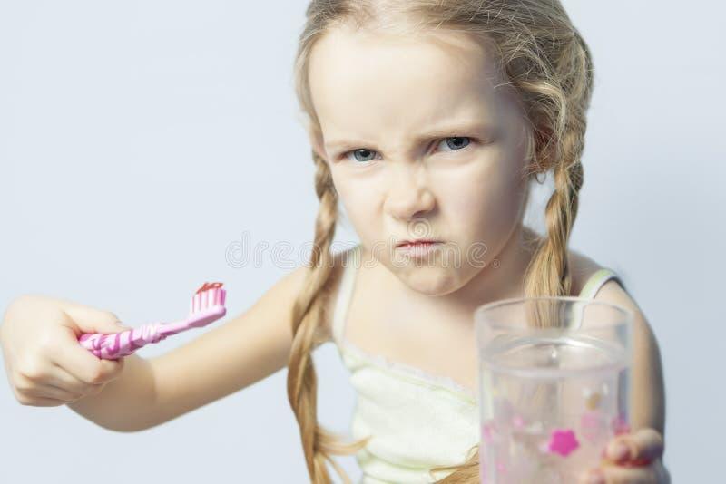 Petite fille fâchée et de furio?s ne voulant pas se brosser les dents photos libres de droits