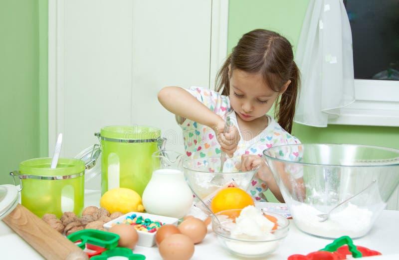 Petite fille faisant cuire dans la cuisine photos libres de droits
