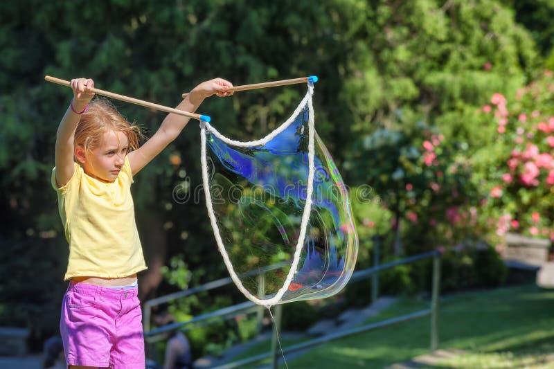 Petite fille faisant des bulles de corde photos stock
