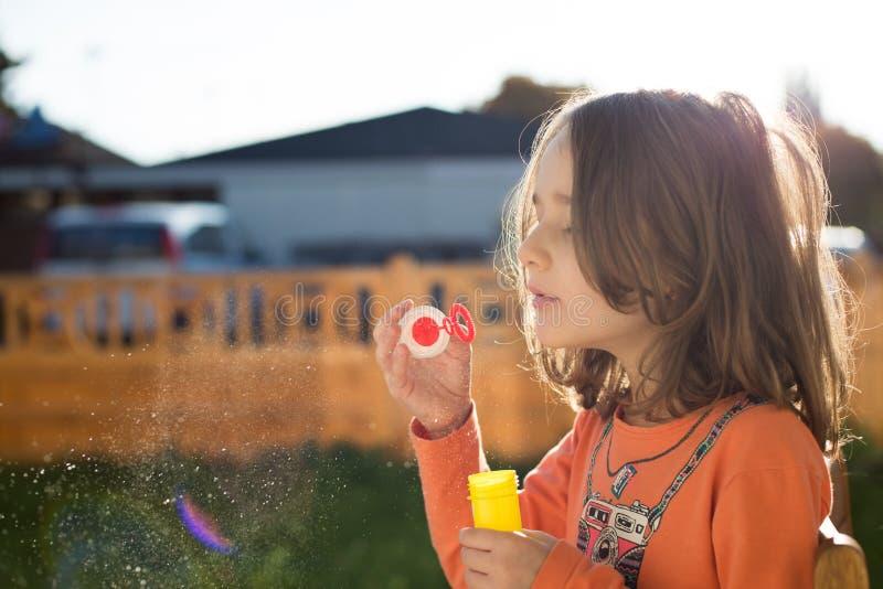 Petite fille faisant des bulles de savon photographie stock