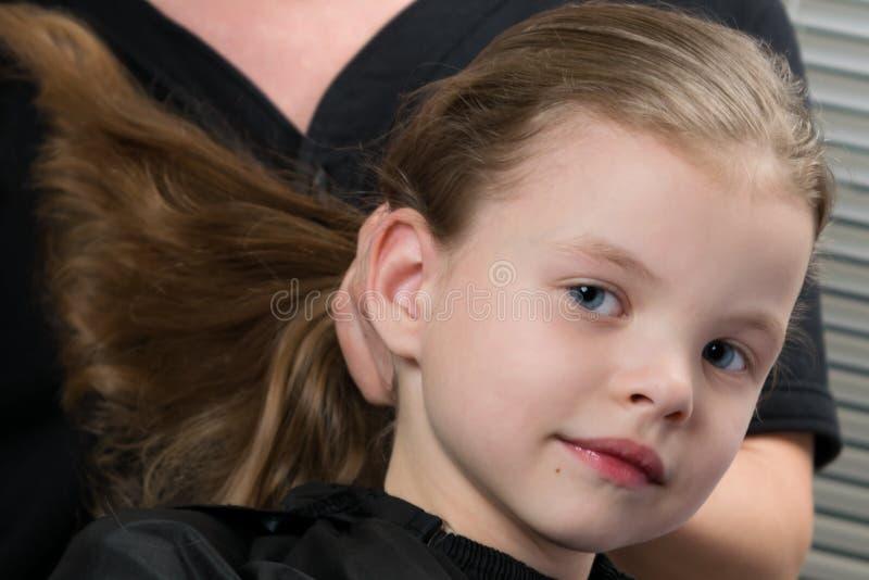 Petite fille faisant des cheveux dénommant, elle sourit photo stock