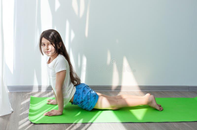 Petite fille faisant la gymnastique sur un museau vert de chien de pose de yoga de tapis  image libre de droits