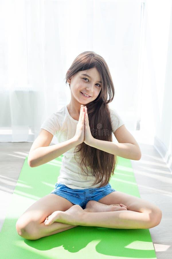 Petite fille faisant la gymnastique sur un tapis vert de yoga en position de lotus photos libres de droits