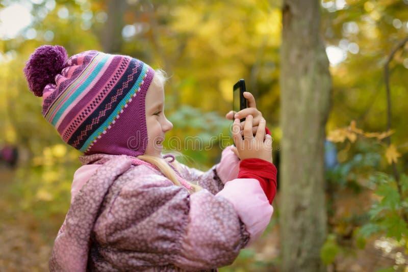 Petite fille faisant la photo ou la vidéo avec le smartphone photos libres de droits