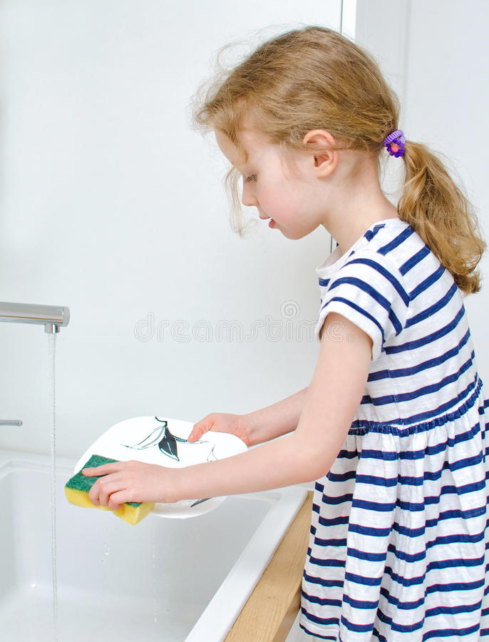 Petite fille faisant la vaisselle photo libre de droits