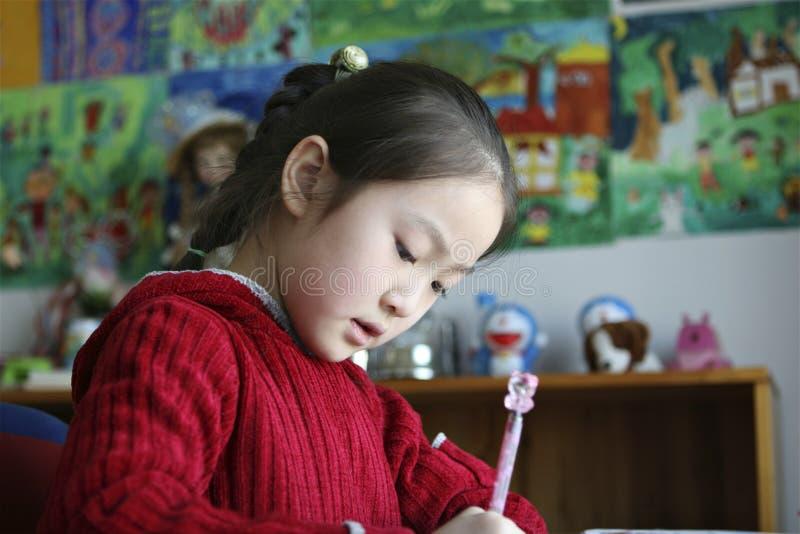 Petite fille faisant le travail à la maison photo libre de droits
