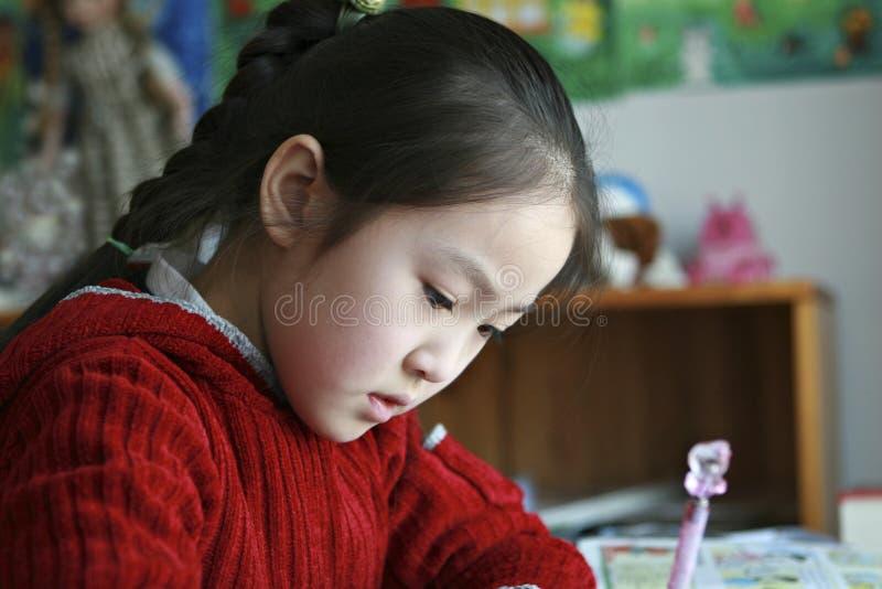 Petite fille faisant le travail à la maison images stock