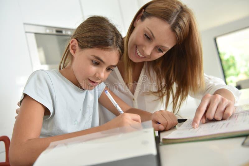 Petite fille faisant le travail avec sa mère l'aidant photos stock