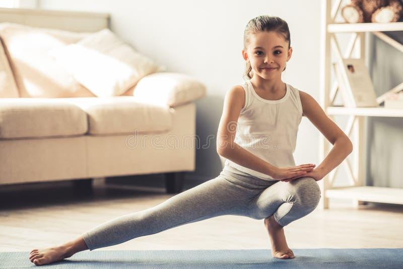 Petite fille faisant le yoga photographie stock libre de droits