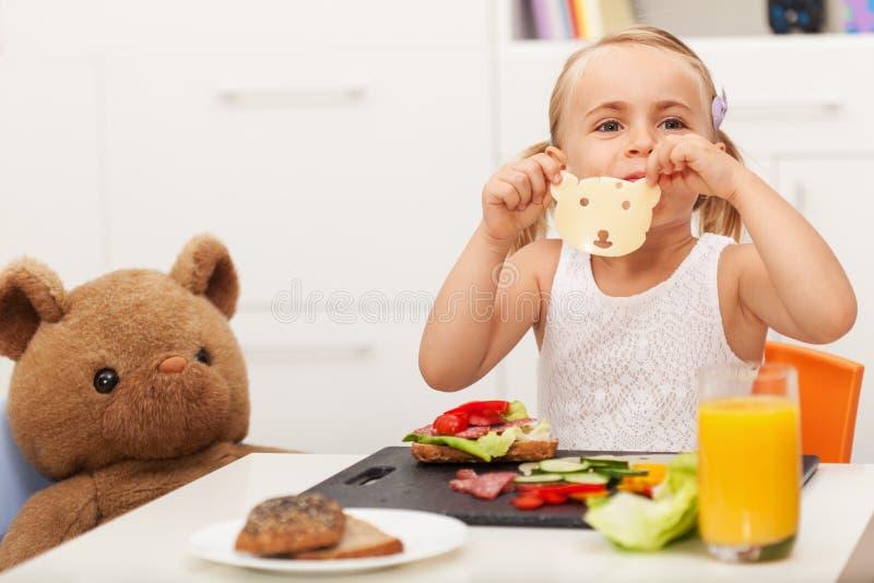 Petite fille faisant un sandwich à son jouet soutenir - avoir un casse-croûte W photos libres de droits