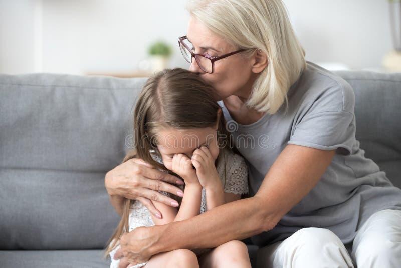 Petite-fille frustrante d'étreinte de grand-maman s'asseyant sur le divan image libre de droits