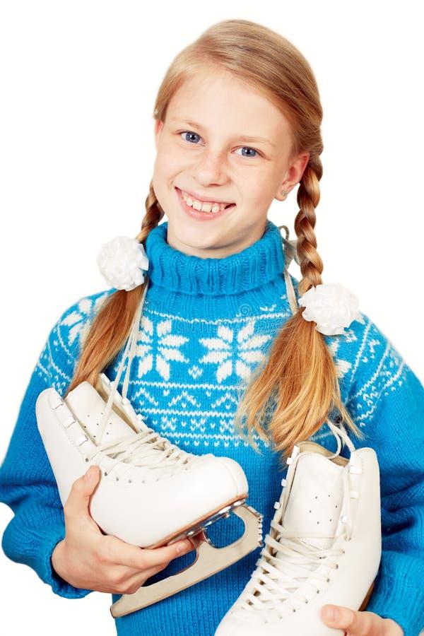Petite fille gaie dans le chandail chaud bleu tenant le chiffre patins photo libre de droits