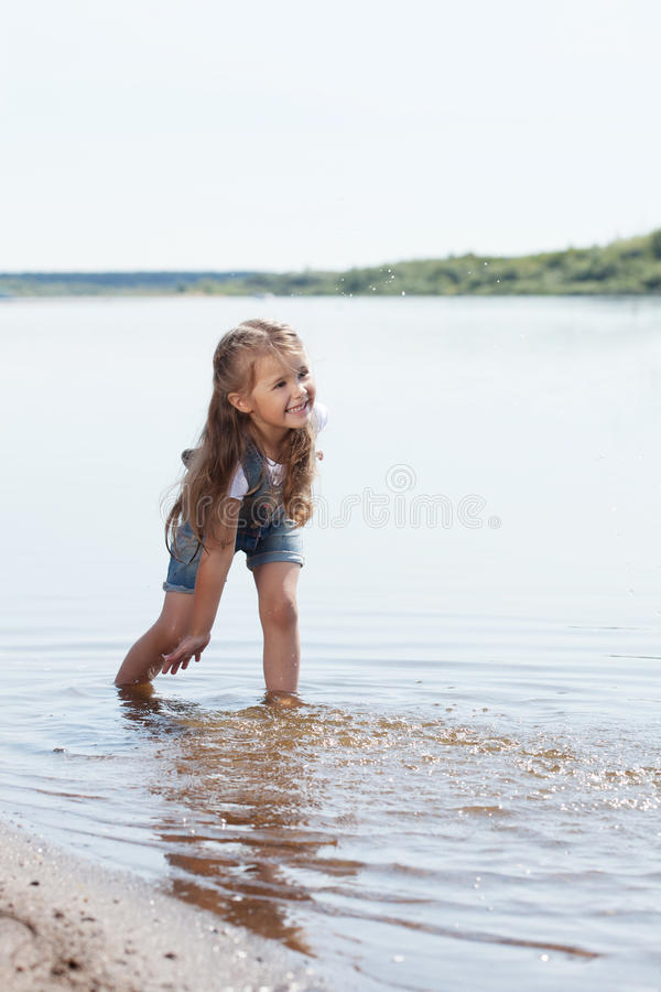 Petite fille gaie jouant dans le lac image stock