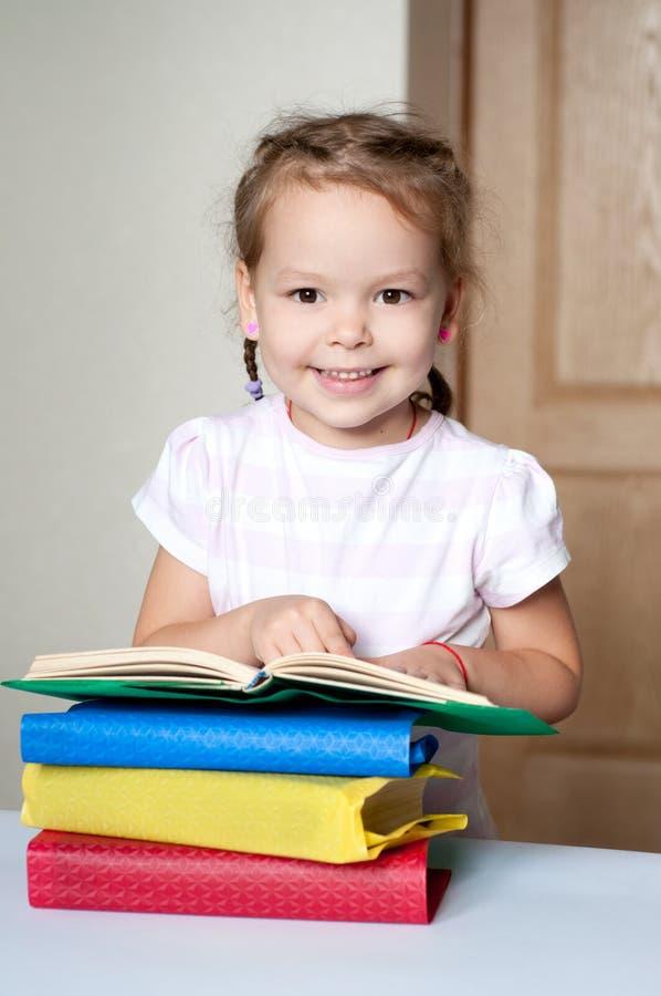 Petite fille gaie mignonne avec des livres images libres de droits