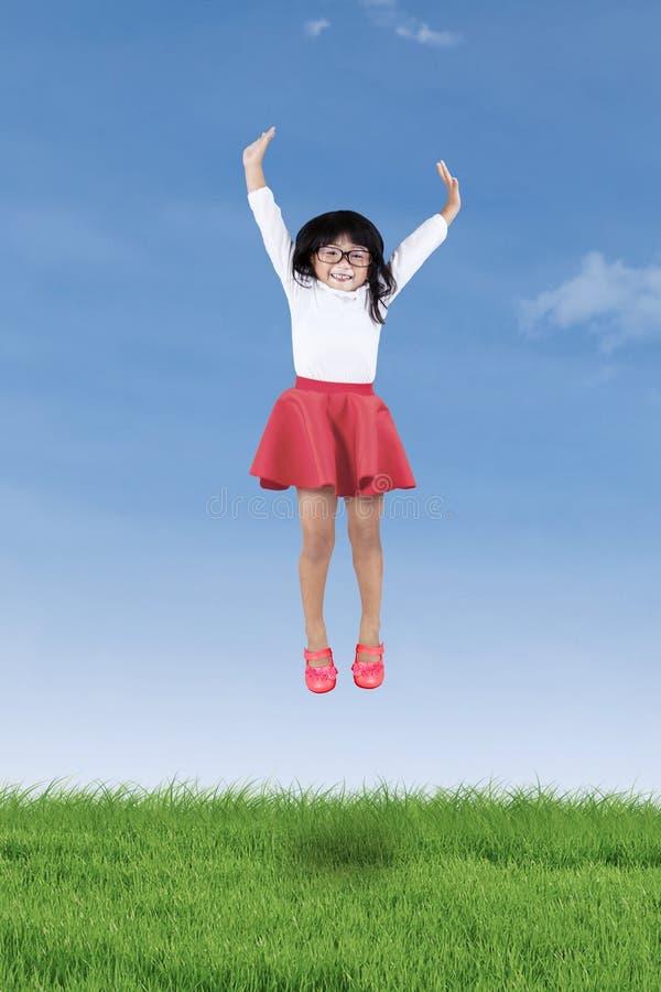 Petite fille gaie sautant sur le pré photo libre de droits