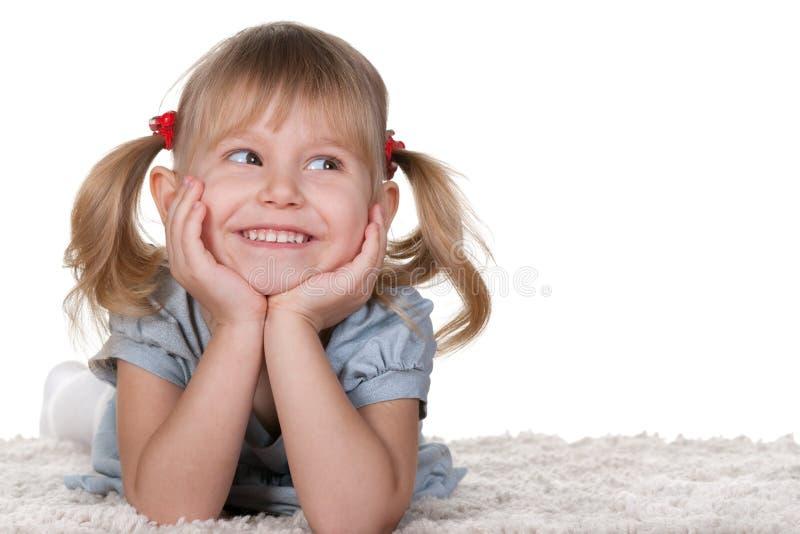 Petite fille gaie se trouvant sur le tapis images stock