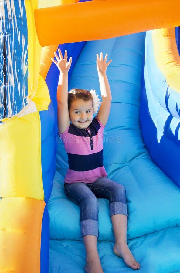 Petite fille glissant vers le bas une glissière gonflable images libres de droits