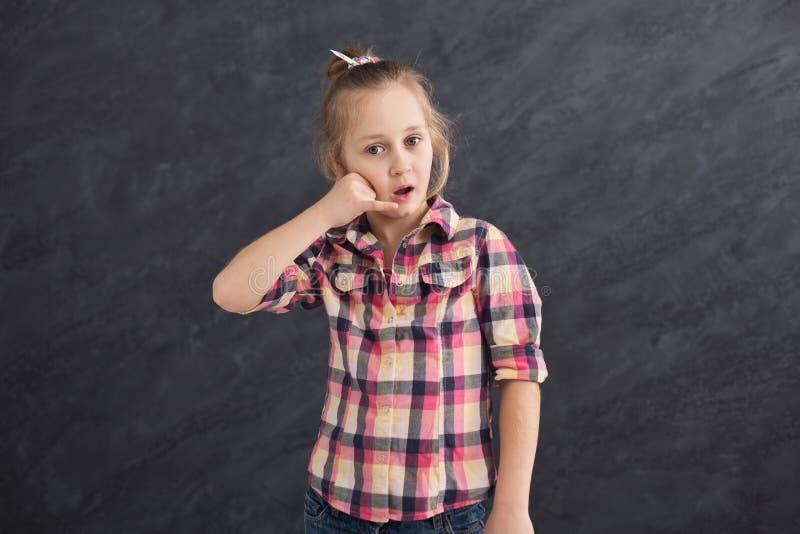 Petite fille grimaçant au fond gris image libre de droits