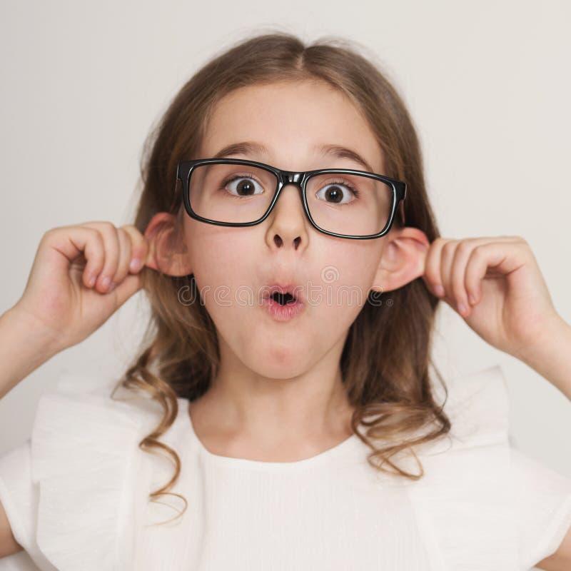 Petite fille grimaçant avec la langue faisant des oreilles dépassant photos stock