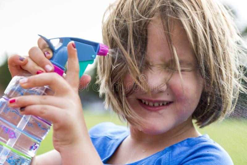 Petite fille grimaçant comme elle pulvérise l'eau sur son visage pour refroidir photo stock