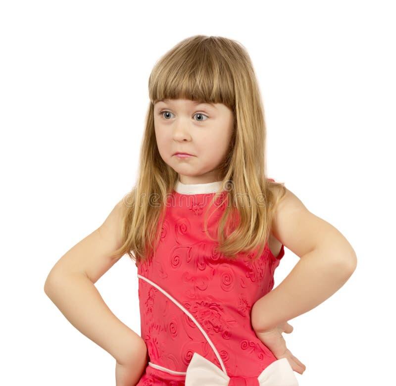 Petite fille grincheuse sur le fond blanc photographie stock