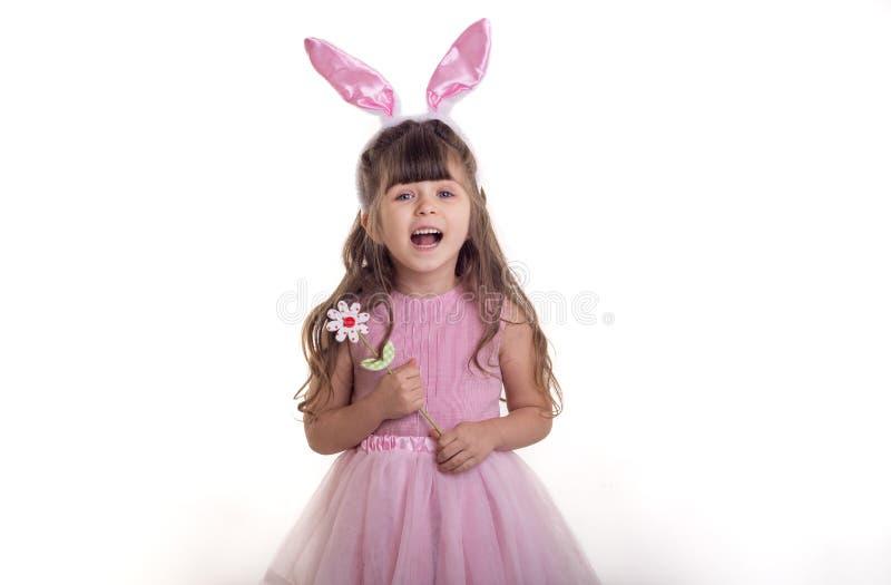 Petite fille habillée comme position de lapin de Pâques sur la fleur blanche de fond et de se tenir Concept de vacances de Pâques photos libres de droits
