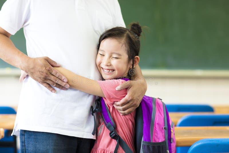 Petite fille heureuse étreignant son père dans la salle de classe images stock