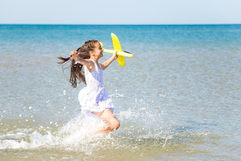 Petite fille heureuse adorable portant une robe blanche fonctionnant par l'eau de mer et jouant avec le jaune à images libres de droits
