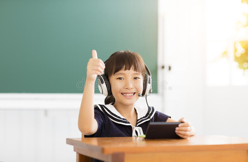 Petite fille heureuse apprenant et montrant le pouce  image libre de droits