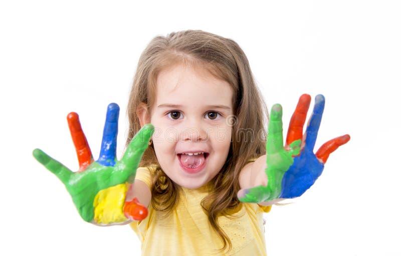 Petite fille heureuse avec des mains peintes en couleurs images libres de droits