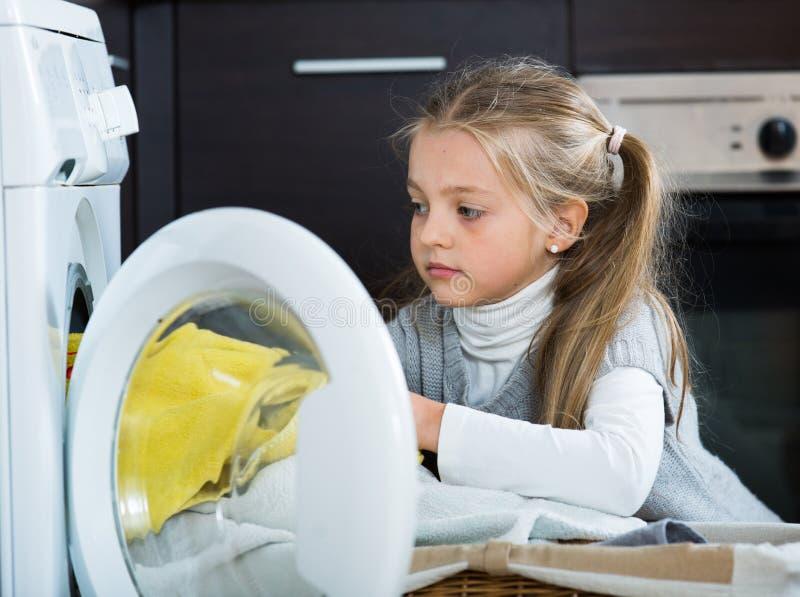 Petite fille heureuse avec des queues de cheval faisant la blanchisserie à l'intérieur photo libre de droits