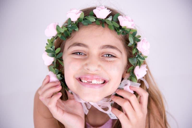 Petite fille heureuse avec des roses autour du visage photos stock