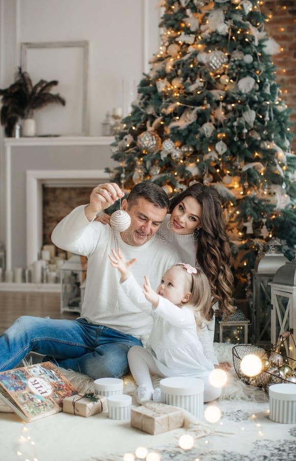 Petite fille heureuse avec la maman et le papa parmi le paysage du ` s de nouvelle ann?e photographie stock