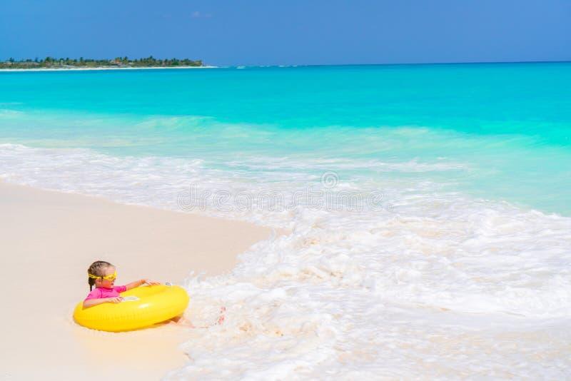 Petite fille heureuse avec le cercle en caoutchouc gonflable ayant l'amusement sur la plage en eau peu profonde de yhe image stock