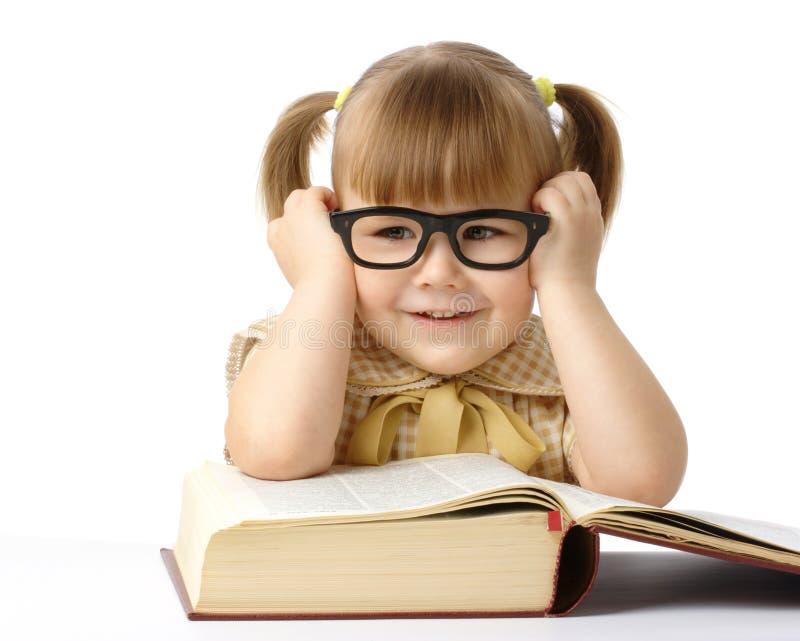 Petite fille heureuse avec le livre portant les lunettes noires images stock