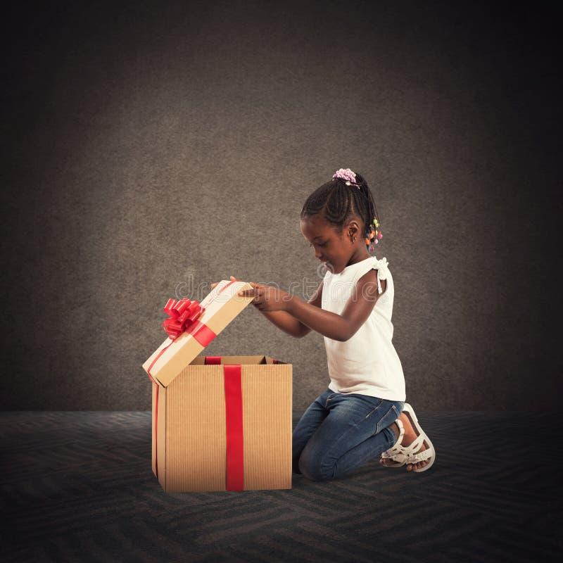 Petite fille heureuse avec un cadeau de Noël photo stock