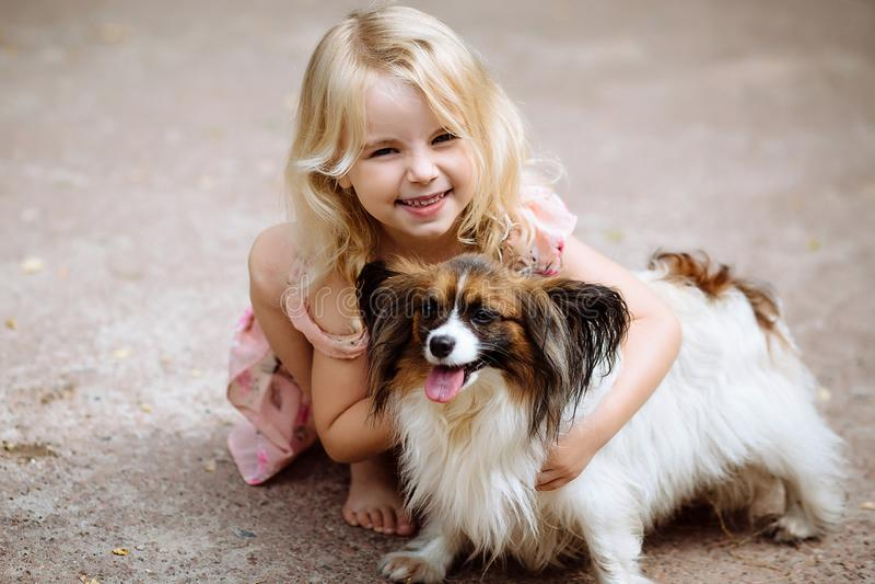 Petite fille heureuse avec un chien se tenant sur la route en parc Petite fille mignonne étreignant un chien, souriant Enfant ave image libre de droits