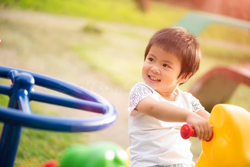 Petite fille heureuse ayant l'amusement sur apprécier de terrain de jeu image libre de droits