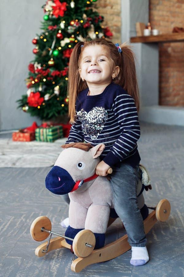 Petite fille heureuse balançant sur un cheval Le concept de Noël image stock